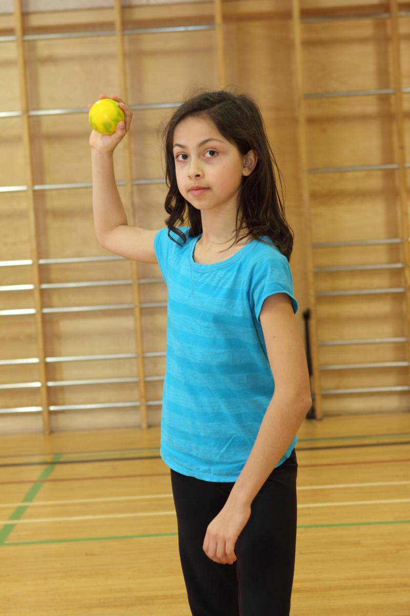 Young girl holding ball in throwing position