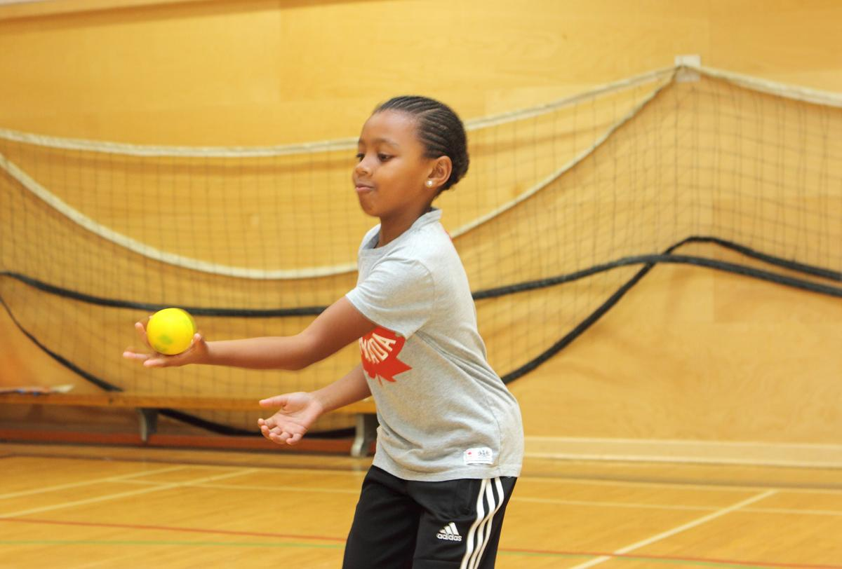 young girl catching a yellow ball with one hand